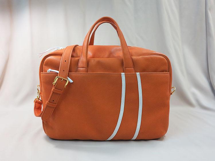 オレンジ色の「チェルシーボストンバッグ」