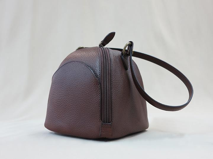 ダークブラウン色の細かな型押しがされた牛革で作ったころりとしたハンドバッグ